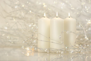 Three white candles with shimmering background for the holidays